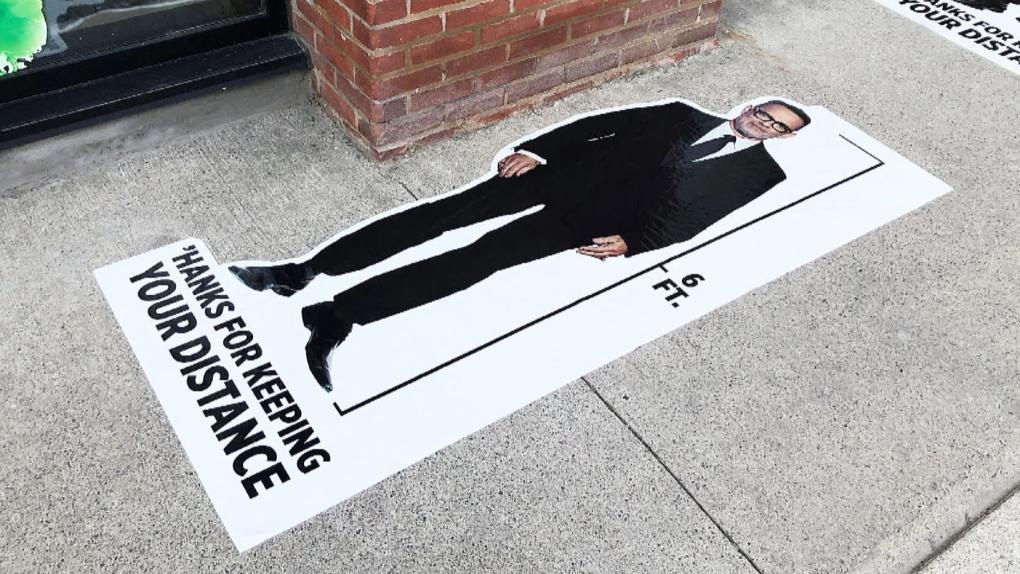 تصویر از یک شرکت در تورنتو با تصویر بزرگ تام هنکس فاصله گذاری اجتماعی را ترویج می دهد